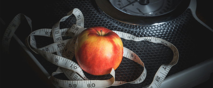 Waage, Maßband und Apfel
